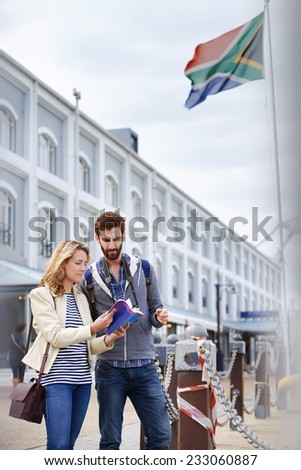 South Africa tourism couple with guide book on vacation holiday - stock photo