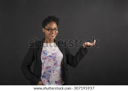 South African or African American black woman teacher or student holding her hand out to the side standing against a chalk blackboard background inside - stock photo