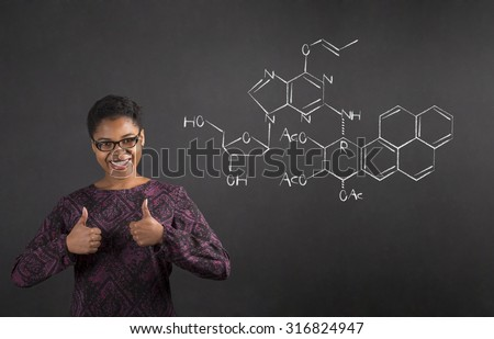 South African or African American black woman teacher or student with a thumbs up hand signal with a science diagram standing against a chalk blackboard background inside - stock photo
