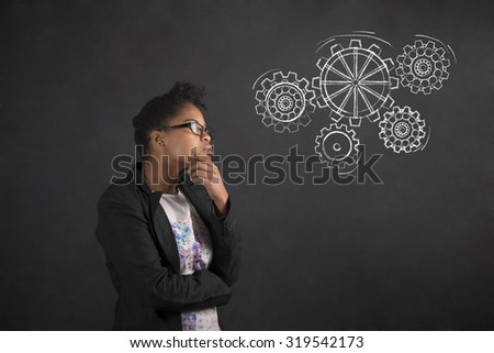 South African or African American black woman teacher or student with her hand on her chin whilst thinking with gears standing against a chalk blackboard background inside - stock photo