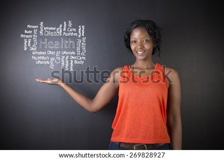 South African or African American woman teacher or student against blackboard background with chalk health diagram - stock photo