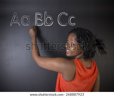 South African or African American woman teacher or student learn alphabet write writing on chalk blackboard background - stock photo