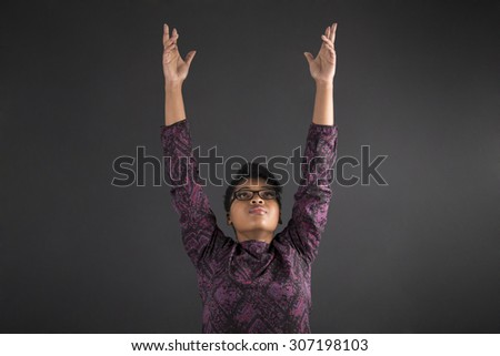 South African or African American woman teacher or student reaching for the sky on blackboard background - stock photo
