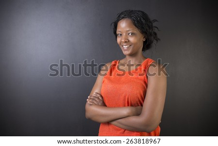 South African or African American woman teacher or student with arms folded on chalk black board background - stock photo