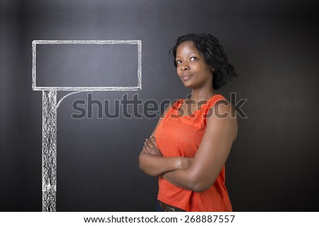 South African or African American woman teacher or student with chalk road advertising sign blackboard background - stock photo