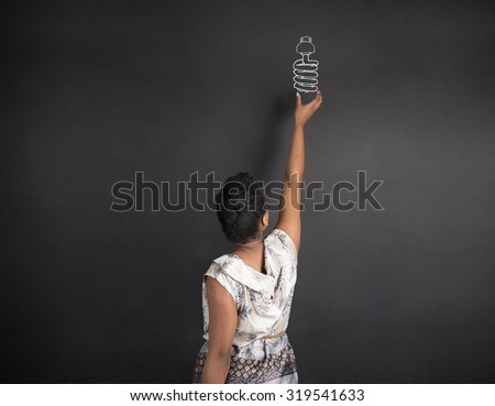 South African or African American woman teacher or student with hand reaching up to a globe on chalk black board background inside - stock photo