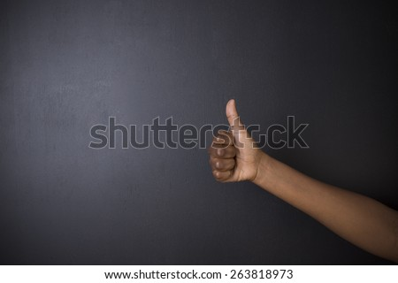 South African or African American woman teacher or student with thumb up on chalk black board background - stock photo