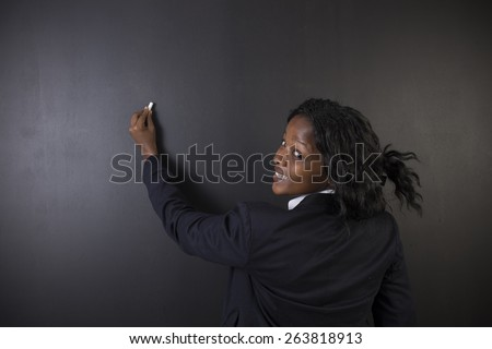 South African or African American woman teacher or student writing on chalk black board background - stock photo
