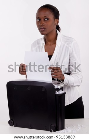 South African woman secretly shredding a document. - stock photo