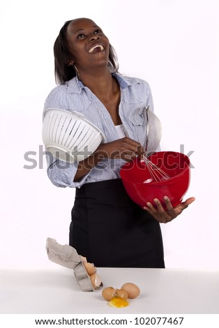 South African woman seeing humor in the mess she made in the kitchen. - stock photo