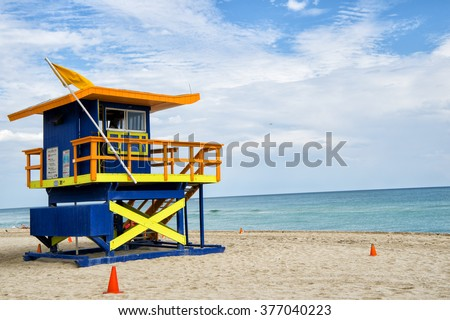 South Beach, Miami, Florida, lifeguard house in a typical colorful Art Deco style on cloudy day with blue sky and Atlantic Ocean in background, world famous travel location - stock photo