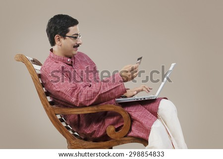South Indian couple with a laptop and credit card - stock photo