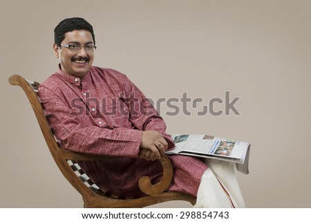 South Indian man sitting on a chair with a newspaper - stock photo