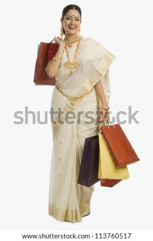 South Indian woman holding shopping bags and smiling - stock photo