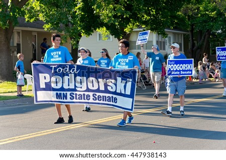 SOUTH ST. PAUL, MINNESOTA - JUNE 24, 2016: Supporters of Minnesota State Senate candidate Todd Podgorski hold an election banner as they march at annual South St. Paul Grande  Parade on June 24.  - stock photo