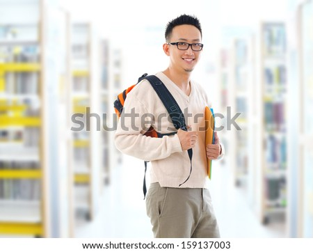 Southeast Asian adult student in casual wear with school bag carrying text books standing inside school library building. - stock photo
