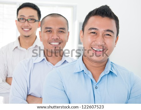Southeast Asian business group standing in office - stock photo