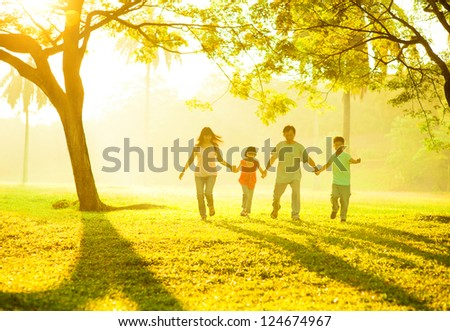 Southeast Asian Chinese family holding hands, running at outdoor green park during sunrise - stock photo