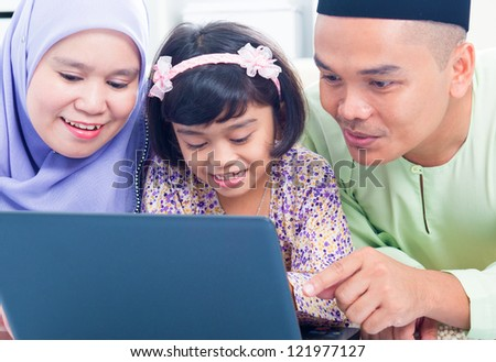Southeast Asian family browsing internet at home. Muslim family living lifestyle - stock photo