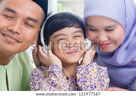 Southeast Asian family listen mp3, sharing headphone. Muslim family living lifestyle - stock photo