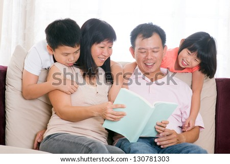 Southeast Asian family living lifestyle. Parents and children reading books at home. - stock photo