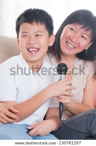 Southeast Asian family living lifestyle. Portrait of a happy Asian family singing karaoke through microphone in the living room - stock photo