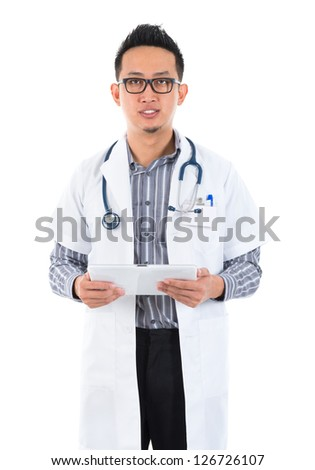 Southeast Asian medical doctor. Serious male medical doctor holding a tablet computer standing on white background. - stock photo