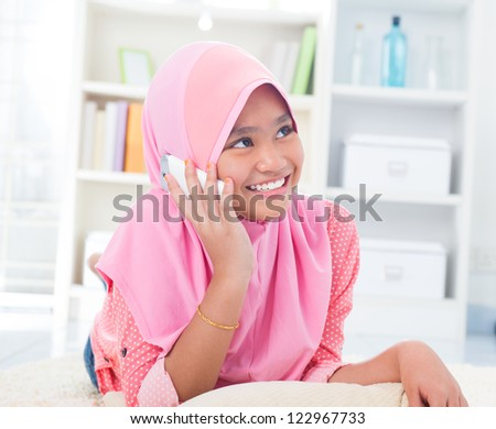 Southeast Asian teenager on the phone at home. Muslim teen girl living lifestyle. - stock photo