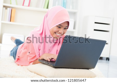 Southeast Asian teenager surfing internet. Muslim teen using notebook at home - stock photo