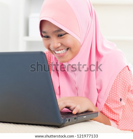 Southeast Asian teenager using notebook at home. Muslim female teen. - stock photo