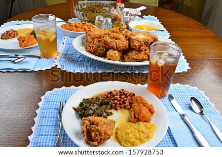 Southern soul food on beautiful old oak dinner table. Wide angle look at plate of fried chicken, creamed corn, collard greens; candied yams and black eyed peas with serving dishes in background. - stock photo