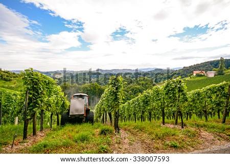 Southern Styria Austria - Grape vines: Tractor in steep vineyard - stock photo