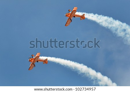 SOUTHPORT, ENGLAND - JULY 23: Two Orange Breitling Bi-planes perform aerobatics and mid air stunts on July 23, 2011 in Southport, England. - stock photo