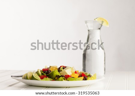 Southwest black bean, lime, cilantro, tomato, and avocado salad on a vintage antique plate next to an old milk jug filled with water - stock photo