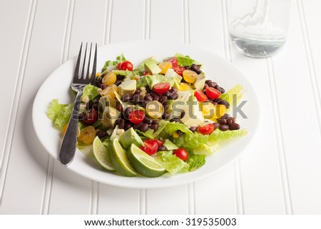 Southwest black bean, lime, cilantro, tomato, and avocado salad on a vintage antique plate with water - stock photo