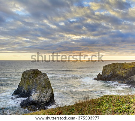 Southwest corner of Yaquina Head, with sea cliffs, the Pacific Ocean, and headland meadows shortly before sunset at the Yaquina Head Outstanding Natural Area, Newport, Oregon. HDR fusion image. - stock photo