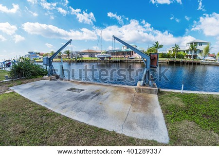 Southwest Florida homes on a canal.  View of canal homes and boat lift along the sea wall on the canal.  - stock photo
