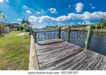 Southwest Florida homes on a canal.  View of canal homes from the boat dock along the sea wall of the canal, leading out to the Gulf of Mexico at the end of the canal.  - stock photo