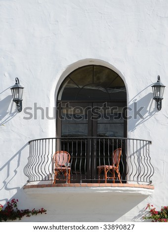 southwest style window and balcony with two chairs - stock photo