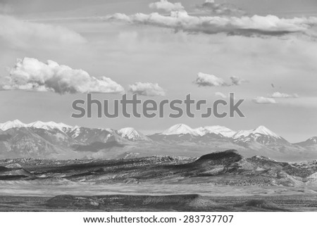 Southwestern landscape with clouds and snow capped mountains in Black and White - stock photo