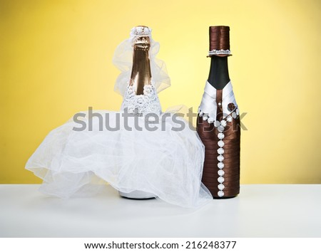 Souvenir bottles for a wedding on a yellow background.Figurines of the bride and groom.champagne - stock photo