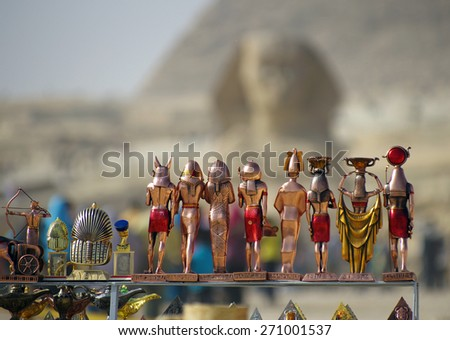 Souvenir figures of the Egyptian gods and pharaohs on background of Sphinx and pyramids. Closeup. - stock photo