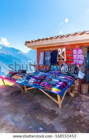 Souvenir market on street of Ollantaytambo,Peru,South America. Colorful blanket, cap, scarf, cloth, ponchos from  wool of alpaca, llama - stock photo
