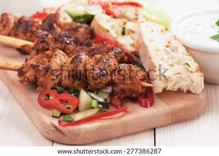 Souvlaki or kebab, meat skewer with toasted bread and fresh vegetable - stock photo