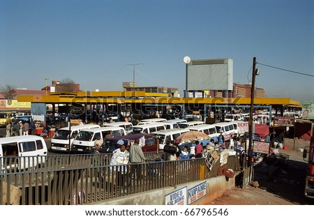 SOWETO, SOUTH AFRICA - JULY 18: Local bus station, July 18, 2005 at Soweto, South Africa. Transport in Africa is by local minibuses. You can get anywhere with these small vehicles. - stock photo