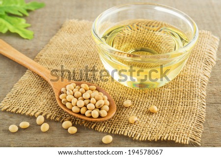 Soy beans and oil on sack - stock photo
