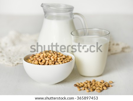 Soy milk in a glass and jar, soybeans on a white table - stock photo