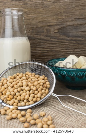 Soy milk,tofu, and soybeans, on wooden background - stock photo