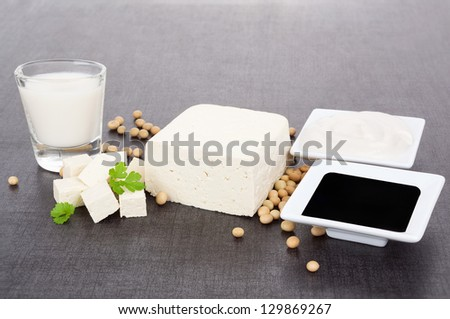 Soy products. Tofu, soy milk, soybeans, soy sauce and soy cream on dark black and grey background. Vegetarian and vegan eating. - stock photo