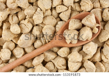 Soya flakes in wooden spoon on soya background - stock photo